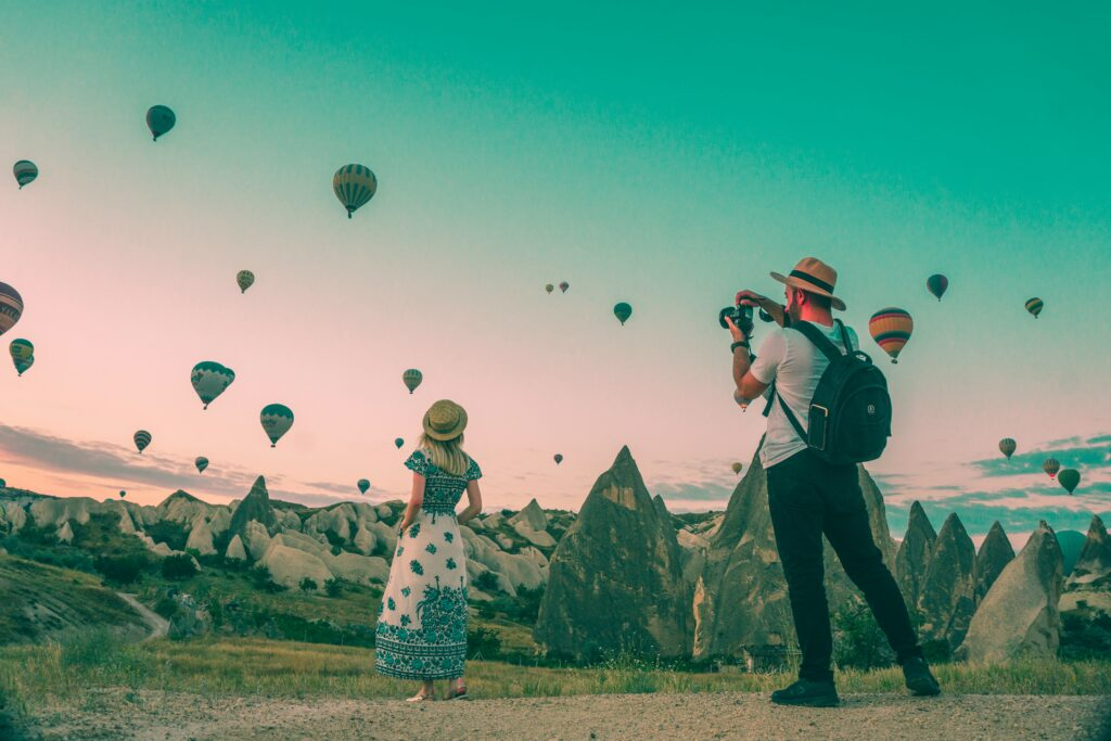 tourists gazing at hot air balloons rising in the dusk
